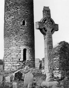 1875:  A round tower and Great Cross in the graveyard at Monasterboice monastery, County Louth, founded by Saint Buite. Figured panels on the South Cross illustrate the Crucifixion, the Last Judgement and the Murder of Abel.  (Photo by Mercer/Sean Sexton/Getty Images)